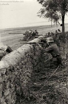 Wehrmacht soldiers fighting and behind them you can see the PaK 40 75mm cannon