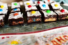 Crazy Brownies-Ingredients:: 1 box Chocolate Cake Mix.. 1/3 cup Evaporated Milk.. 1 stick Butter, Melted.. 9 whole Peanut Butter Cups.. 12 whole Rolo Candies.. 1/2 cup Finely Chopped Pecans.. 1/3 cup M&Ms.. 1/4 teaspoon Salt.. Powdered Sugar (for Sprinkling)..