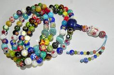 Feng Shui Magic prayer bead mala rosary Feng Shui for Good luck - 108 lampwork beads millefiori murano style + pendant Lucky Cat - Maneki Neko   Miracles happen, and dreams come true! To fulfill desires, happiness and positive mood.  Unique exclusive prayer beads mala of 108 beads (8 mm) - lampwork (style millefiori murano)  These beads emit enormous positive energy, where a melody of bright colors is poured with a waltz of flowers.  Multicolored beads on the tips of the balls are made from…
