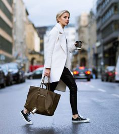 Black converse go with almost anything. We love Caroline Daur's converse look, consisting of leather trousers, a white coat, and a gorgeous brown balenciaga bag.Sweater: Miss Goodlife, Trousers: St. Emile, Shoes: Converse , Case: Balenciaga, Coat: Asos.
