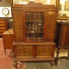 SALE! Now $350. orig. $495 vintage antique burled walnut Rococo Revival china cabinet c. 1930s. burled front. carved detail on top and bulbous legs. glass door with cutout wood trim, two shelves. two doors on bottom with carved trim and original door pulls. a charming way to store and display your china - or anything else! very good condition.