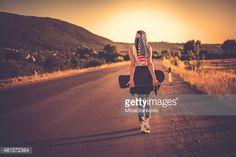 Stock Photo : Young woman with a skateboard on rural road at sunset