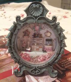 1/144 scale dollhouse miniatures in a clock casing by Sheila A. Nielson.