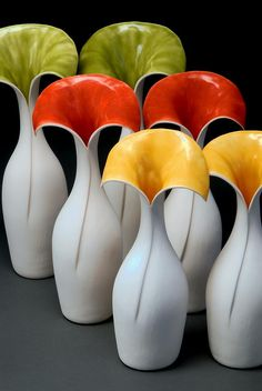 Original bottle is cut, pinched, pulled and curved to create a unique flower. Exterior of vases is purity of porcelain. Interior is translucent glaze. Vase series range 7