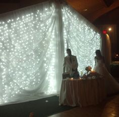"""Light backdrop for wedding head table. Can DIY by draping a frame with white sheets sewn together, then hanging over that, strings of lights about 4"""" apart. Finally drape a swag over it made from sheer white curtains sewn together."""