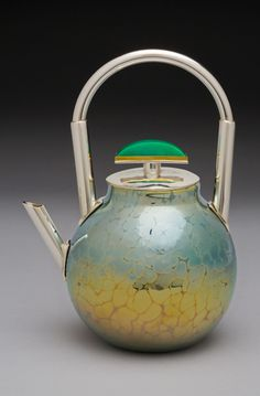 "Chrome Teapot by ELAINE HYDE Vessel is blown ""hammered"" glass. Spout and handle are fabricated sterling silver. Lid is hammered sterling silver with 22 karat gold encasing a hand-cut chrysoprase."