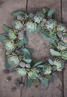 Beautiful Advent wreath made of eucalyptus and white poinsettias.