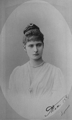 """Princesa Alix de Hesse, depois Imperatriz Alexandra Feodorovna. Ela está olhando para a câmera e está usando um colar de pérolas e uma forma em crescente de gancho de cabelo. A fotografia é assinada e datada """"Alix 1889"""", no canto inferior direito."""