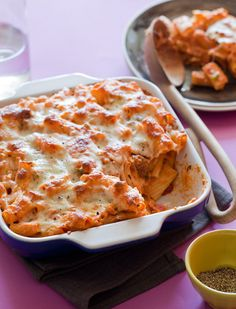 Baked Ziti  Serves 6 to 8    Ingredients:  12 ounces rigatoni pasta  3 tablespoons extra virgin olive oil  3 spicy Italian sausages, casings removed  1/2 yellow onion, diced  1 green bell pepper, seeded and diced  2 garlic cloves, minced  2 1/2 cups homemade or store bought marinara  1 cup part-skim mozzarella cheese  1/2 parmesan, grated  salt and pepper to taste