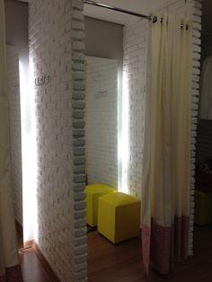 Loja Roupa feminina Amis Arquitetura - Trocadores em tijolo branco com cortinas em tecido branco e rosa e puff para apoio na cor amarela