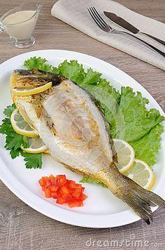 Baked fish Dorado in lettuce leaves with lemon