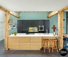 Dit prachtige huis met houten balken zocht een landelijke keuken met moderne uitstraling. Het gerookt eiken van het eiland past erg goed bij de balken. De zwart gelakt eiken hoge kasten komen erg mooi naar voren met deze blauw-groene kleur op de muur. Het eiland is afgemaakt met een keramisch aanrechtblad met een marmer look.