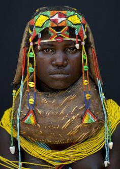 Africa | Mumuhuila tribe - Angola | © Eric Lafforgue.  By the kind of necklace the girl wears, you can say if she is a kid, a teen, a women ready to marry a man, or a married woman.  This one has the huge necklace called Vikeka that she needs to keep from puberty until she marries a man. It may takes 4 years.Then she'll wear a giant neckalce beads, the Vilanda.