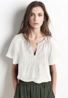 La camisa es de color blanco y un pequeño tamaño. La camisa cuesta quince dólares.