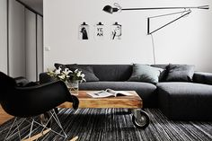 Photo by Swedish Kristofer Johnsson. Grey sofa. Wood floors. Black accents.