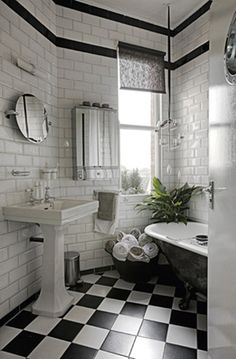 Subway tiled walls, black and white tile floor, and a vintage tub. Design by Holly Sulivan of veryholly