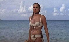 Ursula looks amazing but I do enjoy checking out James Bond too! a edie moment, I wish! Famous Bond Girl Ursula Andress in the famous 'coming out of the water scene' which done later again with Halle Berry. Tous Les James Bond, Thème James Bond, James Bond Girls, James Bond Movies, Ursula Andress, Vanessa Redgrave, Julie Christie, Janet Leigh, Renee Zellweger