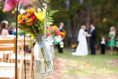 Outside summer wedding with yellow, red, and orange flower arrangements hanging in mason jars.  www.thephotolove.com