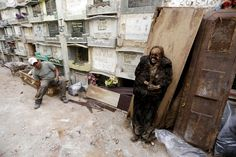 A grave cleaner sits on a coffin next to a mummified body during the exhumation work at the General Cemetery in Guatemala City, April 15, 2015. If a lease on a grave has expired or not been paid, grave cleaners will break open the crypts to remove and rebury the bodies. Any remains that have not been claimed are packed into plastic bags, labeled and stored in mass graves. Bodies that have been stored in the upper crypt are exposed...