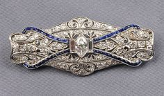 Art Deco Platinum and Diamond Brooch, of navette-form, centering a marquise-cut diamond weighing approx. 0.45 cts., and flanked by baguettes, further set with single-cut diamond melee and French-cut blue stones, millegrain accents, lg. 2 in.