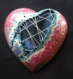 Handmade ceramic heart, wall plaque. Stitched with wire to make it look like a broken heart that has been mended/repaired. The paten that the