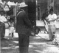 Organ grinder and monkey in front of Rowes pharmacy 1953