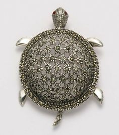 "Sterling Silver Marcasite Sea Turtle Brooch/Pendant with Garnet Eyes Wildthings Ltd.. $225.00. Finely Crafted from .925 Sterling Silver. This brooch has a hidden bail and can be worn as a pendant. THIS DESIGN IS COPYRIGHT PROTECTED ©. A Vintage Collectible Sure to Become a Family Heirloom. To View More Our Related Product Search Amazon Jewelry for ""ODDITY SHOP TURTLE"""