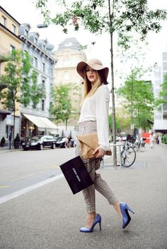 Patterned pants with a white button down shirt, with floppy hat and periwinkle pumps.