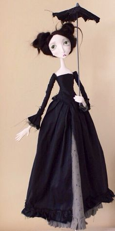 Doll with black hair wearing long black dress & holding umbrella