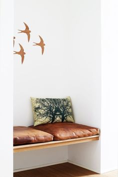 Wooden bench with leather pillows at the entryway - practical when putting on footwear. Decorate the bench with patterned pillows and give the corner a twist with wall decorations.