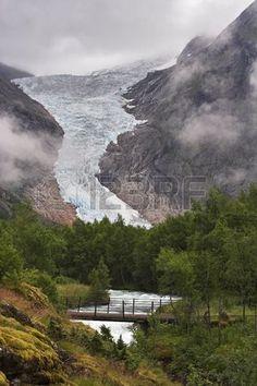 Puente sobre el arroyo en Briksdal glaciar Jostedalsbreen parque nacional Noruega Foto de archivo