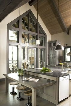 I love the glass, wood ceiling, beams, light fixtures, and colors of this kitchen!
