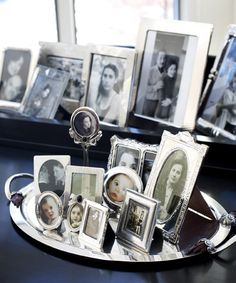 Old and new portraits, in frames of varying heights, develop into a thoughtful vignette when placed on a platter.   - CountryLiving.com