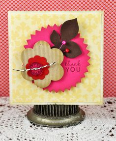 love the color combo of stacked die cut flowers - aalso those cute little pins are actually sewing pins