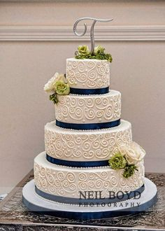 The classic white tiered wedding cake with navy blue ribbon and floral accents #wedding #weddingcake #white #navyblue #cake