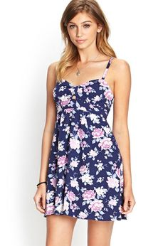 Sweet and femme, this floral print babydoll dress features a cutout front accent and adjustable s...