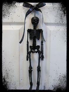 Glittery Black Skeleton Halloween Door Hanger (dollar store skeleton, spray paint, spray adhesive, glitter)