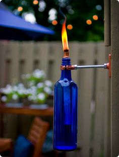 Recycle glass bottles into outdoor torches.