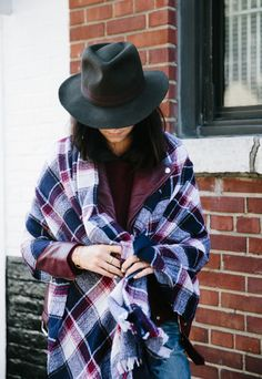 noticed: scarves draped over coats. anna gray is wearing a madewell red, blue and white rangeplaid scarf, red ultimate leather jacket, and the black biltmore® & madewell felt fedora hat.