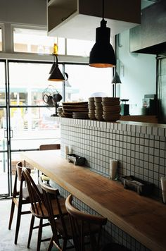 pendant lights, mixed chairs, simple wooden table against tiles - Sajilo Cafe - Japan