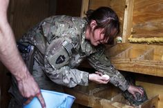 A soldier from an Agriculture Business Development Team attached to the 3rd Battalion (Airborne), 509th Infantry of the 4th Brigade Combat Team, 25th Infantry Division gathers eggs from chickens they are raising
