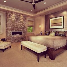 Love the colors.  Rectangular gas fireplace with stone.  Lighting over headboard