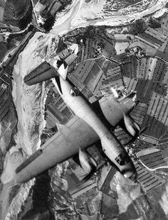 A badly damaged B-26, flying over the Marzabotto rail-bridge in Italy.