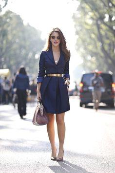 Den Look kaufen: https://lookastic.de/damenmode/wie-kombinieren/mantel-pumps-satchel-tasche-guertel-sonnenbrille-anhaenger-armband/5558 — Goldener Gürtel — Braune Sonnenbrille — Silberner Anhänger — Goldenes Armband — Dunkelrote Leder Pumps — Lila Satchel-Tasche aus Leder — Dunkelblauer Mantel