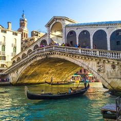Travel Guide to Italy: Gondolas glide under the Rialto Bridge in Venice, Italy.