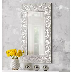 This striking wall mirror features a fluid, mosaic-style frame in a silver finish.