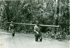 """1944 WWII pipeline installation. Members of the 776th Engineer Petroleum Distribution Company carrying a section of 4"""" pipe through the jungle during a building of a 2,000 mile pipe line from India into Burma."""