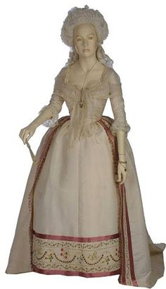 This gown demonstrates the fashionable styles in women's formal dress of the 1780s. The hoop has changed from the square shape of earlier decades to a round profile. A stomacher is no longer needed, because the gown now meets in the front. The cream silk is adorned only at the edges with an embroidered band, ribbon and a stencilled fringe. This restraint in decoration illustrates the growing influence of the Neo-classical style in textile design.