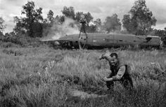 A US soldier running away from a crashed helicopter after rigging it with explosives.      The helicopter crashed near the border of North/South Vietnam, and was blown up to keep the technology out of the hands of the North Vietnamese government, who might have passed it on to the Soviet Union.    Under JFK the number of Americans forces in Vietnam increased from 900 to over 16,000.    Ca Mau, South Vietnam - December 11, 1962.