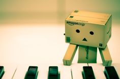 Danbo Playing Piano by NightSheep on DeviantArt Danbo, Miss Piggy, Cardboard Robot, Box Robot, Amazon Box, Robots Characters, Piano Man, Playing Piano, Little Boxes